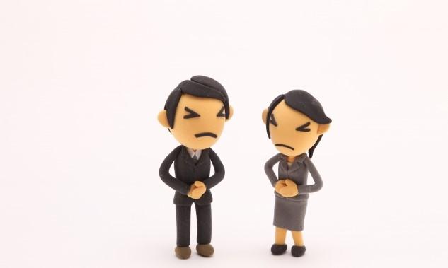 お腹を抑える男女の人形