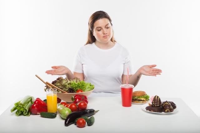 野菜とジャンクフードに迷う白人女性
