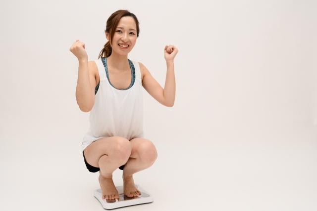 体重計に乗ってガッツポーズをする女性