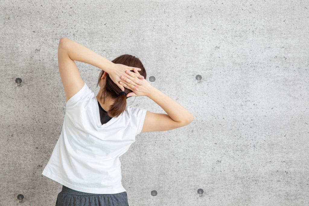頭の後ろで手を組んでる女性